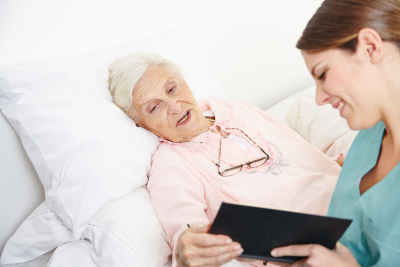 female caregiver and senior woman reading