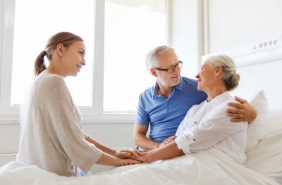 caregiver with senior couple smiling